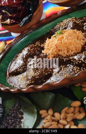 Gros plan de délicieux poulet recouvert de sauce à la mole avec du riz autour des noix, du chocolat et des épices
