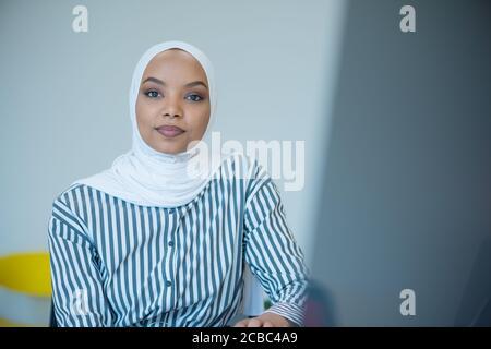 Femme d'affaires musulmane portant le hijab et travaillant à l'ordinateur au bureau. Jolie femme africaine en hijab regardant la caméra et souriant. Concept de plan de travail