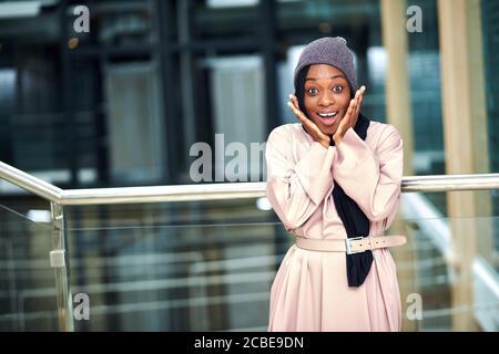 Joyeuse surprise jeune musulmane d'origine africaine vêtue robe longue rose et foulard noir posant dans un cadre urbain sourire à l'appareil photo