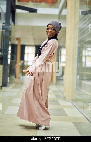Jeune femme musulmane africaine à la mode joyeuse portant une robe longue rose et un chapeau tricoté sur un foulard noir, scène urbaine