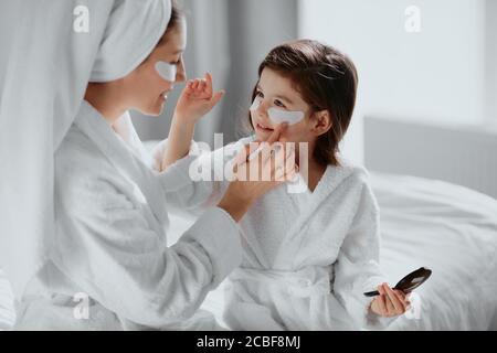 beauté concept. attention la mère attentif utilise des timbres pour les yeux et sa fille dans le masque aussi. parents et enfants intéressés par les procédures de beauté Banque D'Images