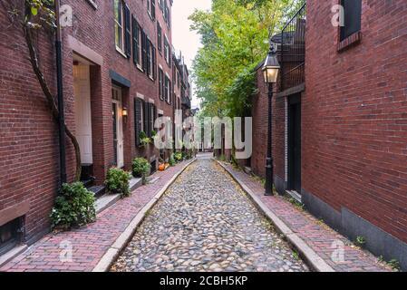 Allée en pierre bordée de maisons en rangée de briques américaines traditionnelles et une lampe à allumage par gaz est allumée un jour d'automne nuageux Banque D'Images