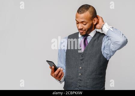homme d'affaires afro-américain professionnel tenant un téléphone mobile