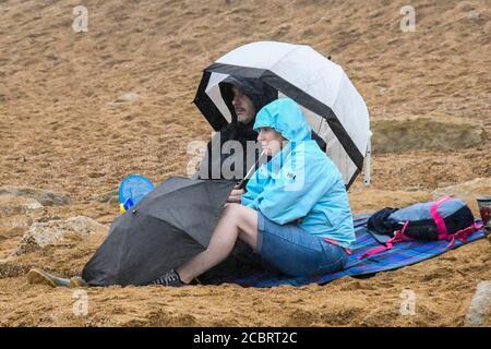West Bay, Dorset, Royaume-Uni. 15 août 2020. Météo Royaume-Uni. Un couple assis sur la plage à l'abri de la pluie sous un parapluie à la station balnéaire de West Bay à Dorset, un après-midi humide. Crédit photo : Graham Hunt/Alamy Live News
