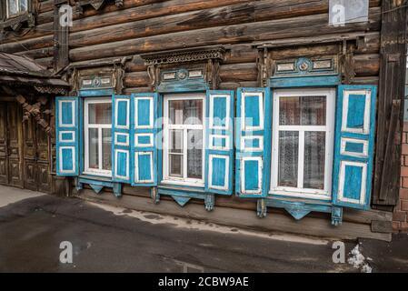 Fenêtres avec volets bleus d'une maison traditionnelle en bois à Irkoutsk, Russie Banque D'Images