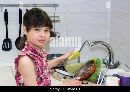 L'enfant lave un tas de vaisselle sale à proximité le lavabo Banque D'Images