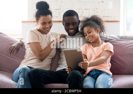 Mignon bonne fille africaine jouant au jeu avec les parents sur le bloc Banque D'Images