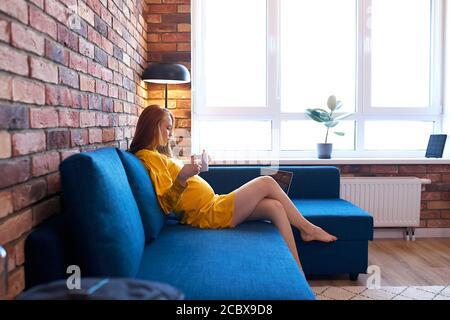 vue latérale sur une femme enceinte à tête rouge attrayante buvant du thé à la maison, femme en robe jaune assis sur un canapé, se reposer