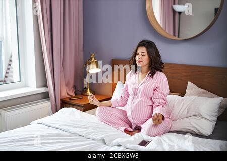 femme enceinte en yoga pose sur le lit, belle-regardant la femme s'attendant à bébé, méditer après se réveiller
