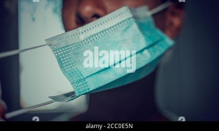 Femme noire mettant ou prenant son masque de visage. Mise au point sélective sur le masque. Arrière-plan flou,