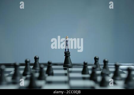 Photo conceptuelle de la stratégie d'affaires - homme d'affaires miniature debout au-dessus du château pion au milieu de l'échiquier