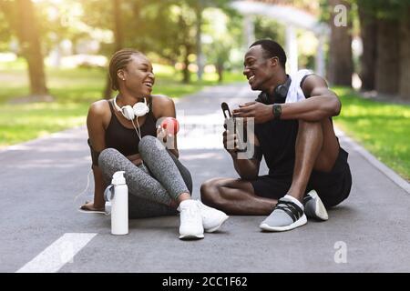 Joyeux couple africain se reposant après avoir fait de l'exercice à l'extérieur, assis sur la voie dans le parc