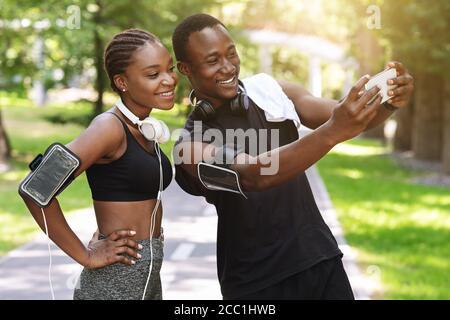 Couple millénaire noir prenant Selfie sur smartphone tout en faisant du sport Ensemble à l'extérieur Banque D'Images
