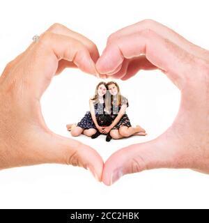 Gros plan carré des sœurs et de leur chien assis dans un geste de coeur de main fait par leur mère et leur père. Banque D'Images