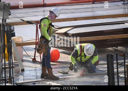 Les ouvriers de la construction portant des vêtements de sécurité et des revêtements de visage font équipe sur le chantier d'un garage de stationnement dans le quartier de Rainey Street, près du centre-ville d'Austin, Texas. Banque D'Images