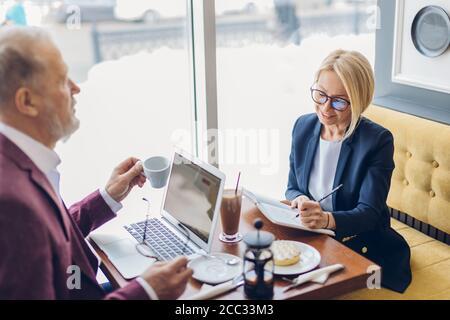 charmante femme blonde et vieil homme prenant le petit déjeuner et discutant d'un plan d'affaires. gros plan photo. concept de loisirs Banque D'Images