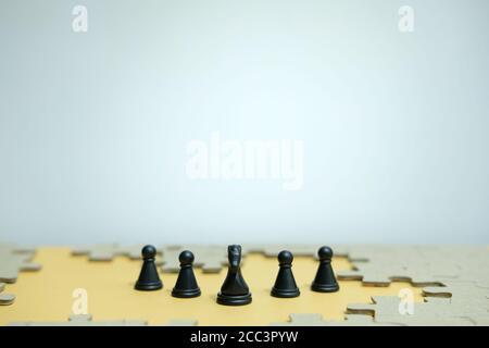Photo conceptuelle de la stratégie d'affaires - une ligne de cheval pièces d'échecs au milieu d'une armée et d'un puzzle casse-têtes