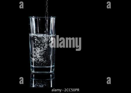 Verser de l'eau dans le verre sur fond noir Banque D'Images