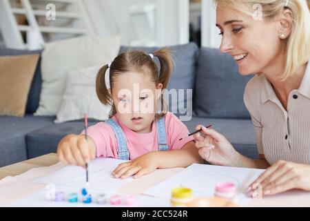 Petite fille avec le syndrome de Down apprendre à peindre à la table avec sa mère l'aidant dans la chambre Banque D'Images