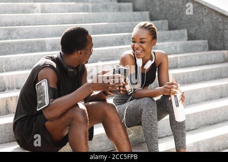 Posez le couple noir en prenant le repos après l'entraînement en plein air, assis sur l'escalier urbain
