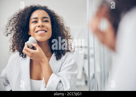 Jeune femme heureuse effectuant une procédure d'exfoliation Banque D'Images