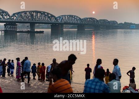 Des pèlerins hindous se rendent au Ganga Ghat de Dakshineswar le long du fleuve Hooghly avec le pont Vivekananda Setu en arrière-plan à Kolkata (Calcutta), en Inde. Banque D'Images