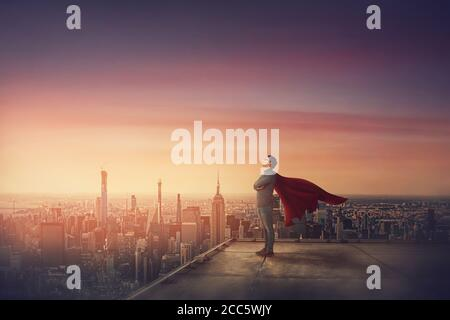 Scène de coucher de soleil conceptuelle, un homme d'affaires avec Red cape se tient confiant sur le toit à l'air déterminé comme un super-héros sur l'horizon de la ville. Ambition et l Banque D'Images