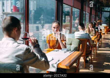 Un jeune couple boire du vin dans un restaurant près de la fenêtre.