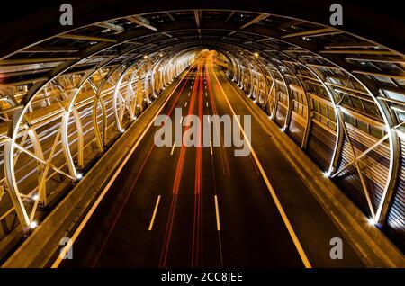 Tunnel de verre à plusieurs lignes au sol pour autoroute. Lignes de vitesse des voitures en mouvement dans un moderne, basé sur le tunnel de verre photographié la nuit.
