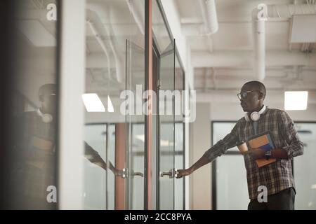 Jeune homme africain en vêtements décontractés ouvrant la porte de la salle du conseil qu'il vient à la réunion