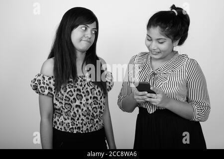 Jeune Perse regardant en colère de jeunes heureux Perse en surpoids femme en utilisant le téléphone Banque D'Images