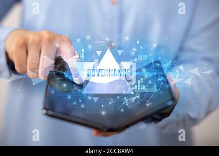 Businessman holding a smartphone pliable avec inscription de la gouvernance, concept d'entreprise