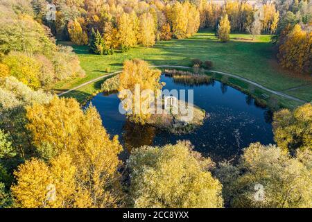 magnifique paysage de parc d'automne avec petit étang entouré d'arbres jaunes colorés. vue aérienne
