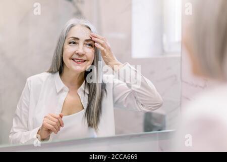 Jolie femme âgée avec de longs cheveux gris, portant une chemise blanche, regardant son visage dans le miroir de salle de bains, et appliquant de la crème anti-rides ou cosmétique