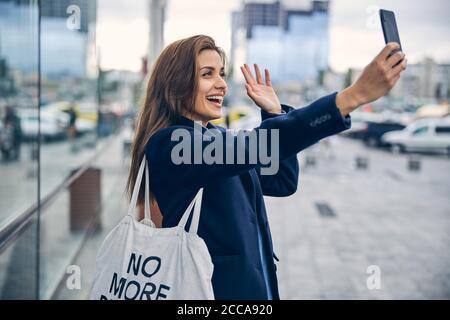Jeune belle dame riant et agitant la main dans l'appareil photo