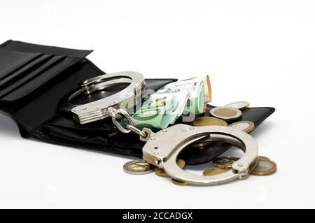 Gros plan des menottes, de l'argent en papier et des pièces de monnaie dans un portefeuille en cuir noir