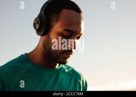 Portrait d'un athlète afro-américain portant un casque sans fil. Gros plan d'un homme de fitness debout à l'extérieur et à l'écoute de musique.