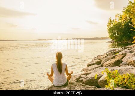 Cours de yoga à l'extérieur dans un parc naturel près du bord du lac. Une femme assise dans le lotus pose méditant par l'eau dans le soleil du matin se fait jour au lever du soleil. Méditation