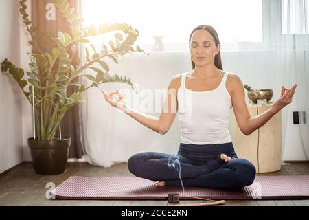 calme yogi femelle s'asseoir sur le sol dans la pose de lotus, méditer à la maison pendant la quarantaine, chaque matin commence du yoga, elle utilise des bâtons d'arôme
