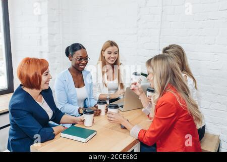 Les femmes le travail d'équipe et team building concept. Démarrage positif partenaires féminines dans les tenues de discuter des idées de nouvelle stratégie de développement à Banque D'Images