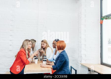 Processus de travail de l'équipe. Groupe multiracial de jeunes femmes collaborant en open space office. L'entraîneur mentor rousse parler aux jeunes, l'enseignement aud Banque D'Images