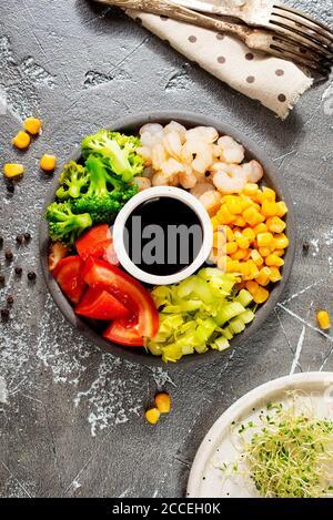 Ingrédients de cuisine sur l'assiette. Vue de dessus. Légumes, épices, crevettes, sauce pour la cuisson.