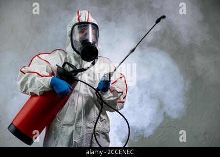 Désinfecteur professionnel dans un équipement de protection individuelle NBC combinaison d'epi, gants, masque, nettoyage de l'espace isolé avec désinfectant en aérosol sous pression W