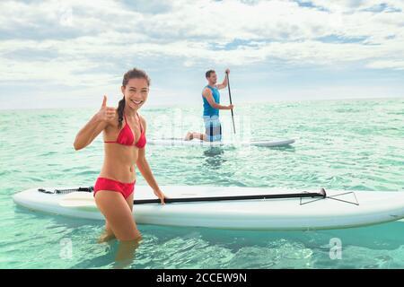 Paddleboard Beach les gens sur des paddle-up surfant dans l'océan sur la plage d'Hawaï. Couple mixte de race femme et homme caucasien appréciant le sport nautique
