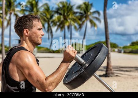 Centre de remise en forme en plein air, un sportif masculin s'entraîner sur le T-bar en été. Homme entraînement de force d'entraînement de bras biceps muscles avec lourd