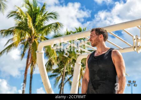 Centre de remise en forme en plein air, un athlète masculin s'entraîner sur des bars à singes en été. Entraînement d'homme