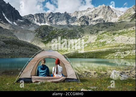 Deux jeunes femmes dans la tente touristique sur la vallée verte contre le lac turquoise et la chaîne de neige de montagne. Randonneurs extrêmes dans le camp. Trekking lifesyl