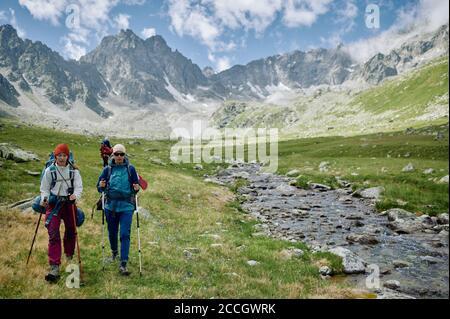 Deux femmes randonneurs marchent avec des bâtons de trakking au bord de la rivière parmi les montagnes. Les touristes extrêmes dans la nature sauvage. Voyages domestiques et trekking. Local vers Banque D'Images