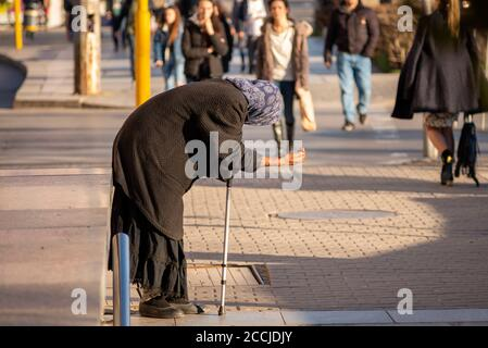 Les gens qui approchent une vieille femme âgée tenant un bâton et Mendier de l'argent dans les rues de Sofia Bulgarie