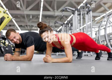 jeunes athlètes caucasiens, hommes et femmes, effectuant des retouches pendant la croix entraînement à la salle de gym